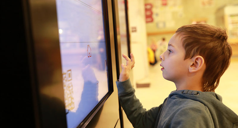 kid using touch screen in museum